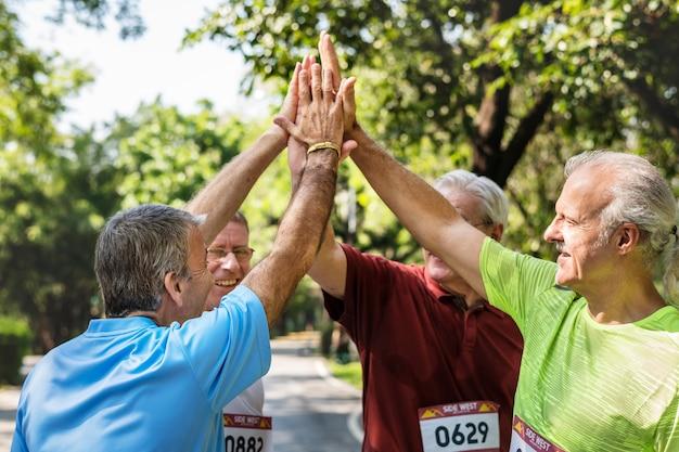 Groupe d'athlètes seniors donnant un high five