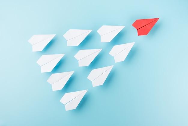 Groupe d'avion en papier blanc et un avion rouge sur bleu