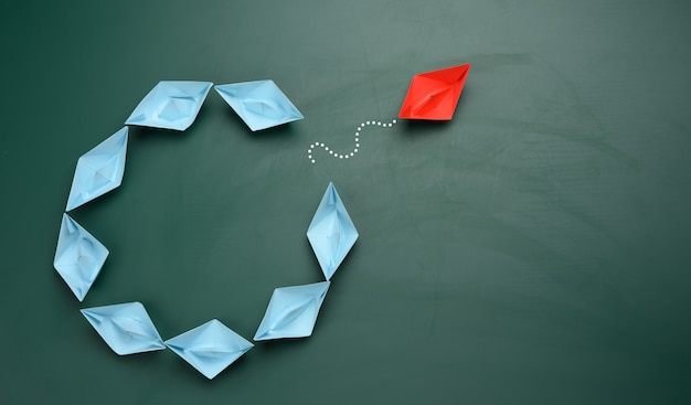 Un groupe de bateaux en papier bleu navigue dans une direction, un rouge navigue dans la direction opposée. le concept d'une personnalité extraordinaire, pour agir à l'encontre des fondements de la société