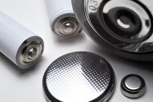 Groupe de batteries de différents types et tailles sur fond blanc
