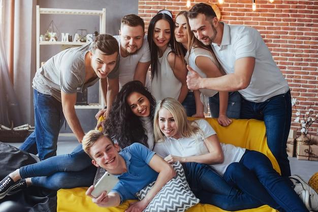 Groupe de beaux jeunes faisant selfie dans un café, meilleurs amis filles et garçons s'amusant ensemble, posant un style de vie émotionnel