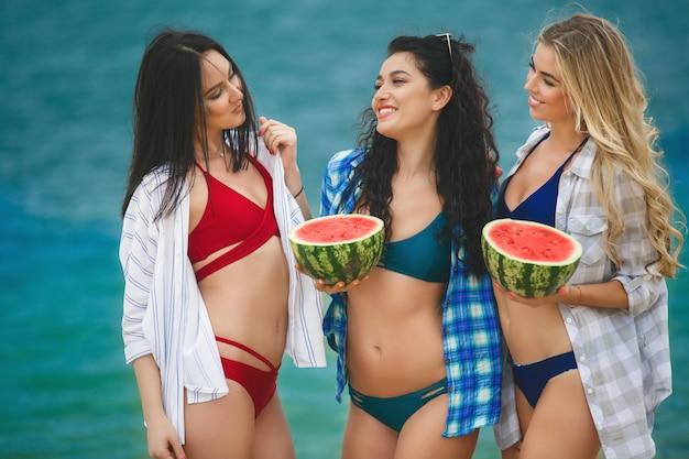 Groupe de belles femmes gaies se reposant avec la pastèque sur la plage. rire des copines au bord de la mer en s'amusant. jolies femmes bronzant