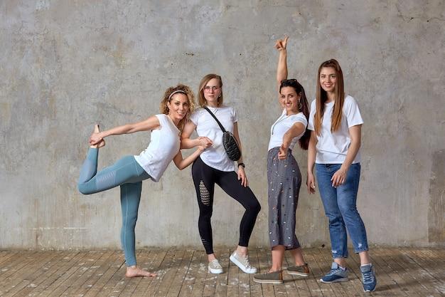 Un groupe de belles filles posant contre le mur. concept d'équipe, amitié, rencontre d'amis.
