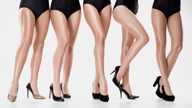 Groupe de belles jeunes femmes posant au studio sur fond blanc. concept de beauté féminine. les chaussures à talons sur les modèles caucasiens
