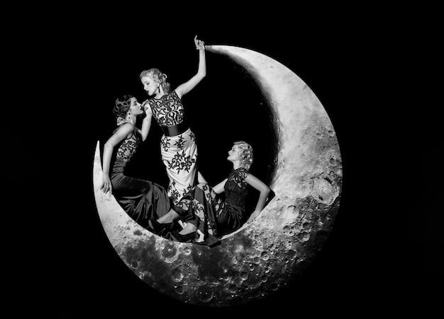 Groupe de belles jeunes femmes posant sur le croissant de lune en robe élégante longue soirée sur fond noir