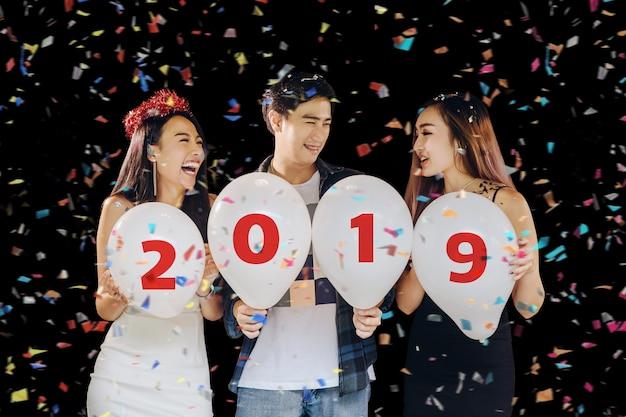 Groupe de belles jeunes gens asiatiques célébrant la saint-sylvestre