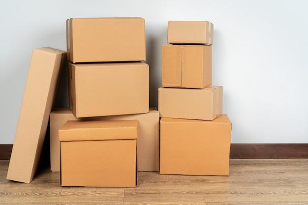 Groupe de boîtes en carton brun sur plancher en bois