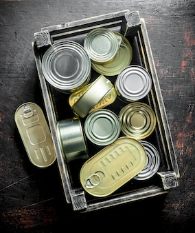 Groupe de boîtes fermées en aluminium avec des aliments en conserve dans une boîte. sur une surface rustique sombre
