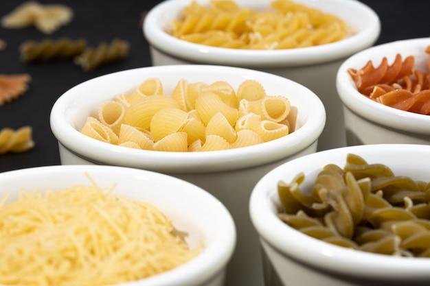 Groupe de bols avec assortiment de pâtes non cuites. un plat méditerranéen