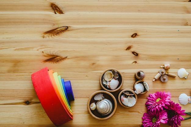 Groupe de bols ronds en bois remplis de coquillages et de fleurs violettes