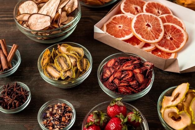 Groupe de bols en verre contenant du kiwi séché, des poires, des fraises, des oranges et des épices aromatiques debout sur une table de cuisine en bois foncé