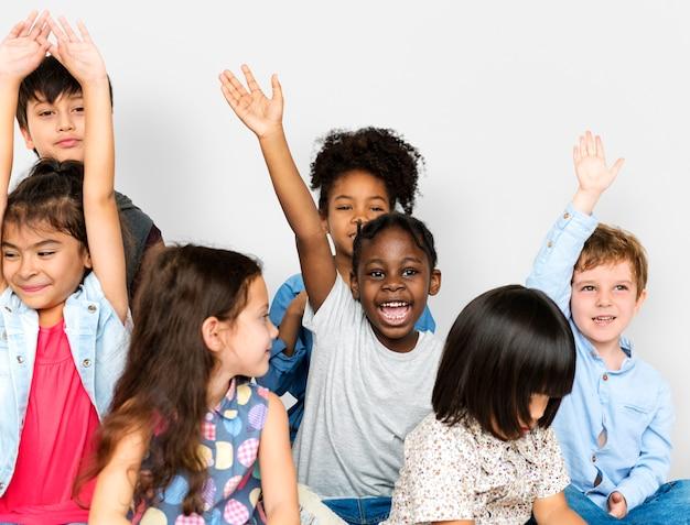 Groupe de bonheur petits enfants assis sur le sol