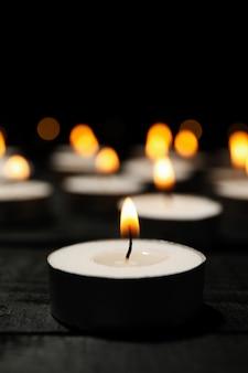Groupe de bougies allumées sur fond noir, close up