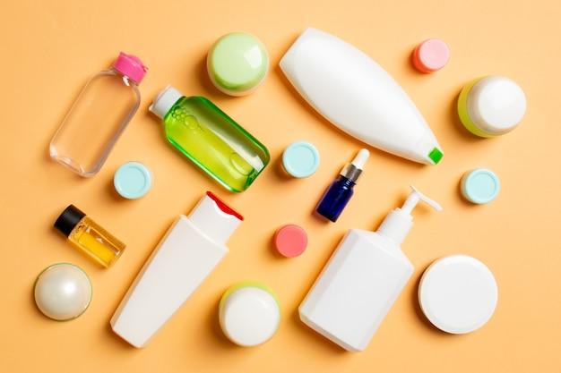Groupe de bouteille de soins du corps en plastique composition à plat avec des produits cosmétiques sur un espace vide de surface colorée pour votre conception