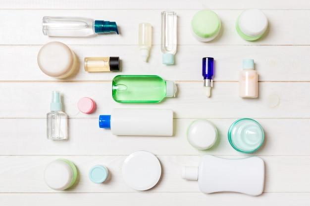 Groupe de bouteille de soins du corps en plastique composition à plat avec des produits cosmétiques sur fond en bois espace vide pour votre conception. ensemble de conteneurs cosmétiques blancs, vue de dessus avec espace de copie.