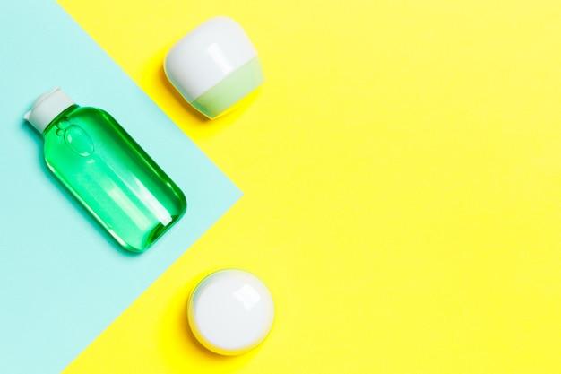 Groupe de bouteille de soins du corps en plastique composition à plat avec des produits cosmétiques sur fond jaune et bleu espace vide pour votre conception. ensemble de conteneurs cosmétiques blancs, vue de dessus avec espace de copie.