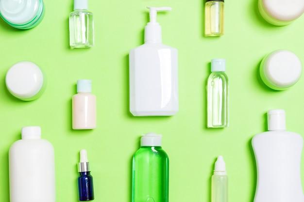 Groupe de bouteille de soins du corps en plastique composition à plat avec des produits cosmétiques sur fond vert espace vide pour votre conception. ensemble de conteneurs cosmétiques blancs, vue de dessus avec espace de copie.
