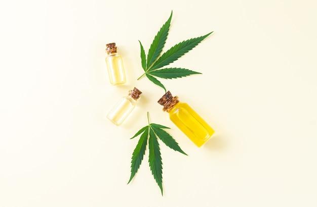 Groupe de bouteilles en verre avec huile de cannabis cbd, teinture de thé et feuilles de chanvre. vue de dessus, mise à plat