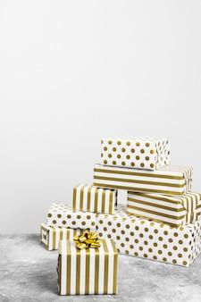 Groupe de cadeaux en papier blanc et or sur fond gris