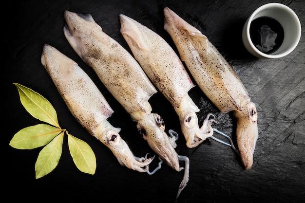 Groupe de calamars frais à côté d'un bol avec de l'encre et des feuilles de laurier