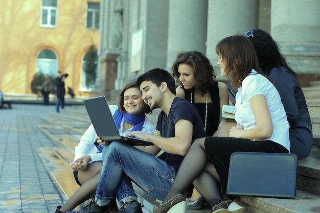 Groupe de camarades avec des livres et un ordinateur portable