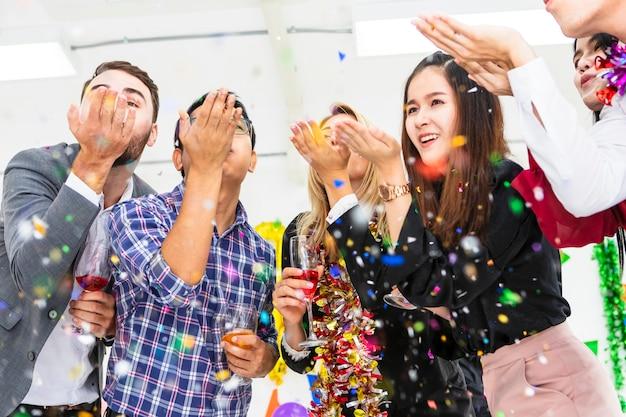 Groupe de célébrer soufflant des confettis colorés et l'air heureux