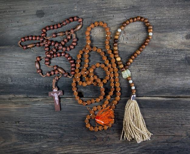 Groupe de chapelets de différentes religions sur bois rustique