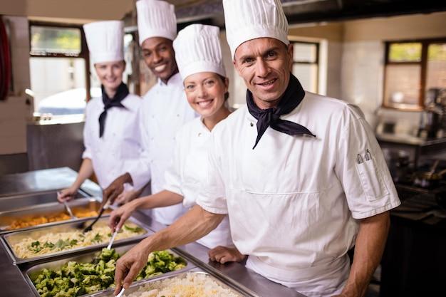 Groupe de chefs en train de mélanger des mets préparés dans la cuisine