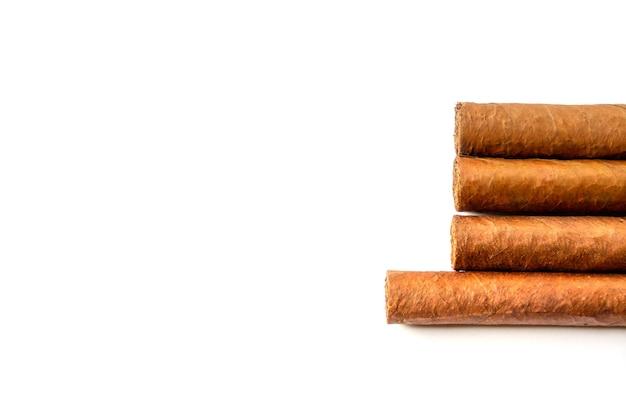 Groupe de cigares cubains bruns isolés sur une surface blanche