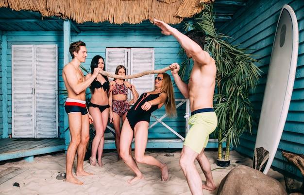Groupe de cinq amis célébrant dans leur maison de plage d'été