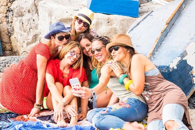 Groupe de cinq belles filles jeunes et gentilles prenant selfie pictire avec technologie smartphone. robe d'été pour le concept de vacances et d'amitié. les gens colorés et souriants apprécient la vie et les vacances
