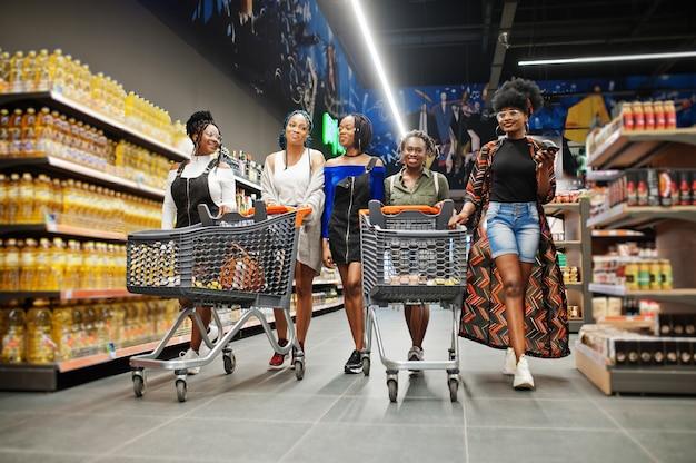 Groupe de cinq femmes marchant dans un supermarché avec des caddies