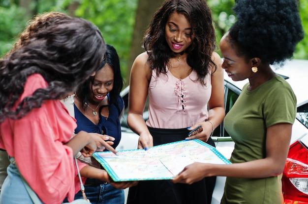 Groupe de cinq femmes de voyageurs heureux regardant la carte contre la voiture