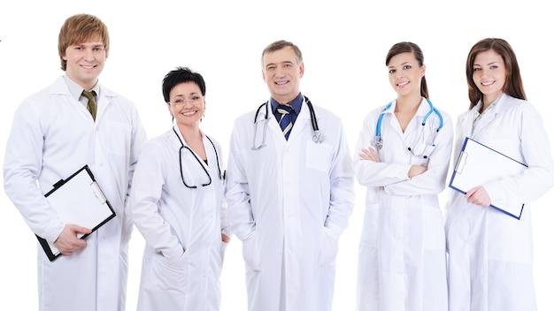 Groupe de cinq médecins réussis en riant debout ensemble