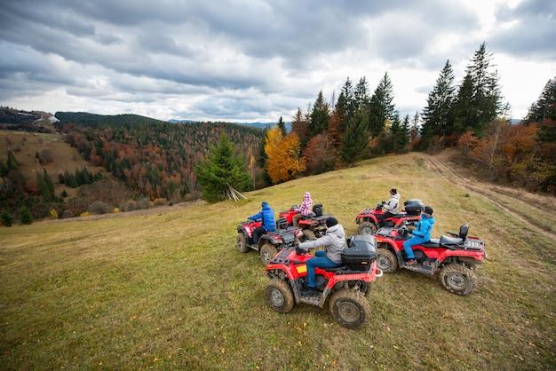 Groupe de cinq personnes conduisant des quads sur la colline