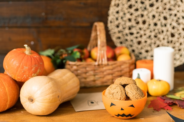 Groupe de citrouilles mûres, bol en plastique halloween orange avec des biscuits sur des bougies et panier avec des pommes