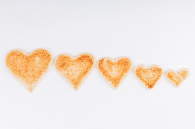 Groupe de coeurs de pain grillé avec un coeur brisé ensemble sur fond blanc