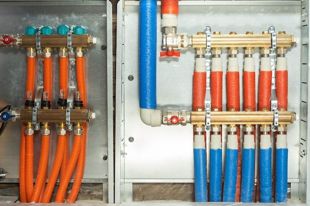 Groupe collecteur et pompe pour plancher chauffant avec vannes servomoteur et débitmètre, installé dans une maison privée