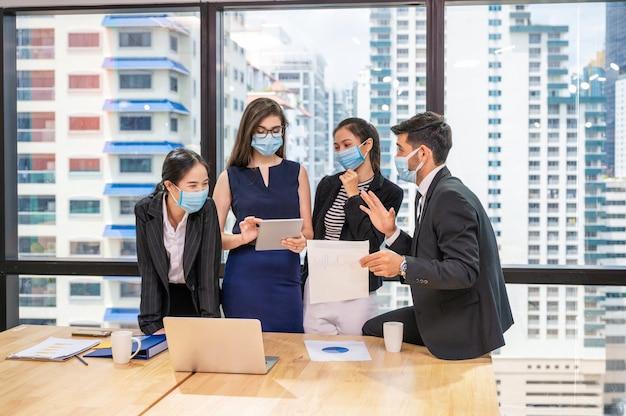 Groupe de collègues d'affaires multiethniques se réunissant et discutant du plan d'affaires de l'entreprise au bureau. équipe d'hommes d'affaires portant un masque facial lors de la consultation dans un nouveau bureau normal
