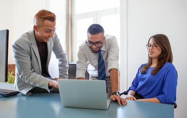Un groupe de collègues sur un ordinateur portable reçoit de bonnes nouvelles