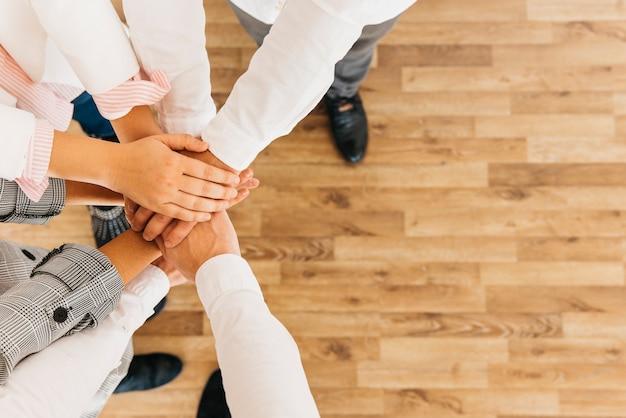 Groupe de collègues réunissant les mains