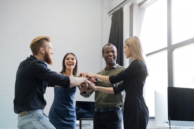 Groupe de collègues souriants, main dans la main