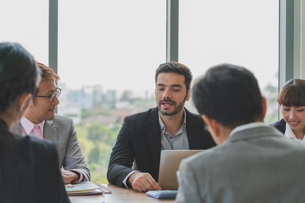 Groupe de collègues de travail réunis pour discuter de projet d'entreprise sur le lieu de travail