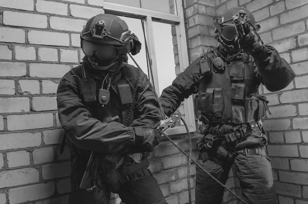 Un groupe de combattants des forces spéciales prend d'assaut le bâtiment par la fenêtre. séances de formation de l'équipe swat