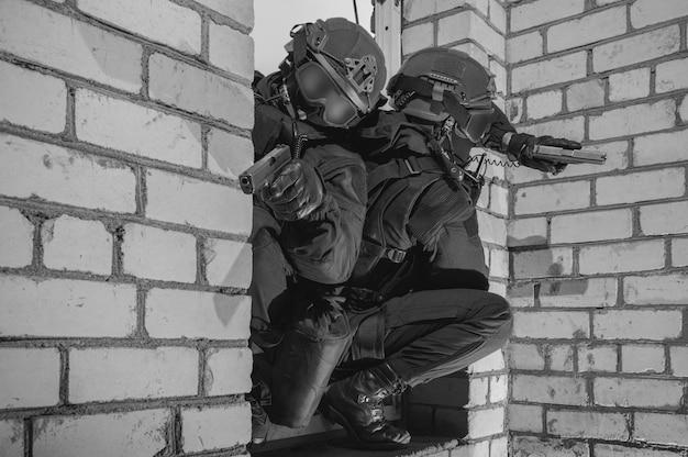Un groupe de combattants des forces spéciales prend d'assaut le bâtiment à travers la fenêtre des médias