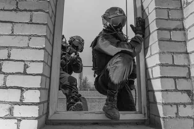 Un groupe de combattants des forces spéciales prend d'assaut le bâtiment à travers les grimpeurs de la fenêtre. technique mixte