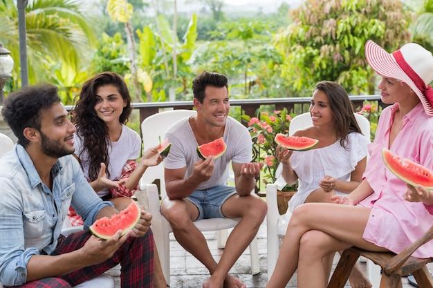 Groupe de communication d'amis de jeunes mangeant une pastèque
