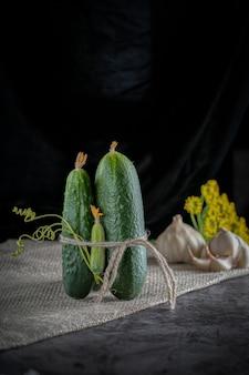 Un groupe de concombres sur la table avec indrigentov pour le salage: ail, aneth. fond sombre.