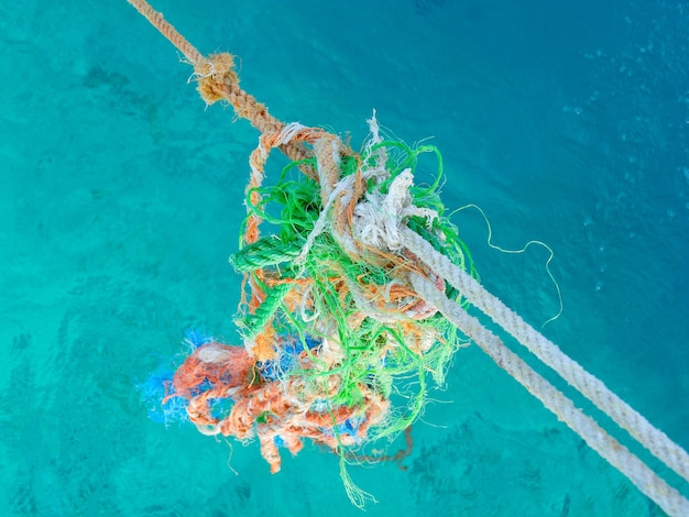 Groupe de cordes de style torsadé usés multicolores sur fond bleu de l'eau