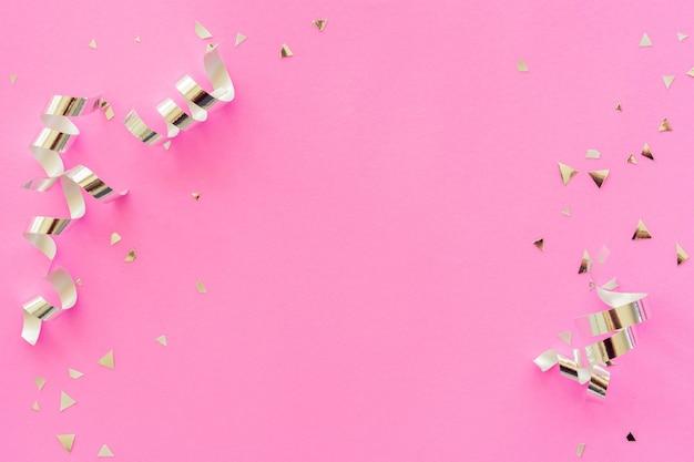 Groupe de couleur argentée de ruban roulant et de confettis sur fond rose pour le concept de la saint-valentin